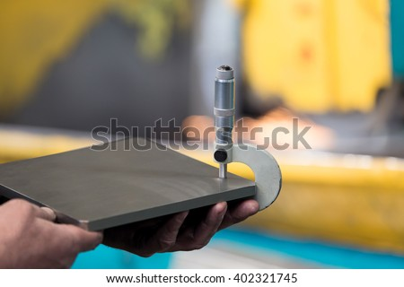Factory worker measure detail with digital caliper micrometer during finishing metal working on horizontal surface grinder machine - stock photo