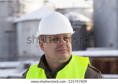 Factory worker on the oil tank background