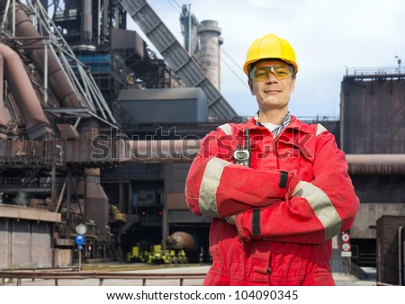 Factory worker posing in front of a blast furnace, wearing safety gear, including a hard hat, goggles and fire retardant coveralls - stock photo