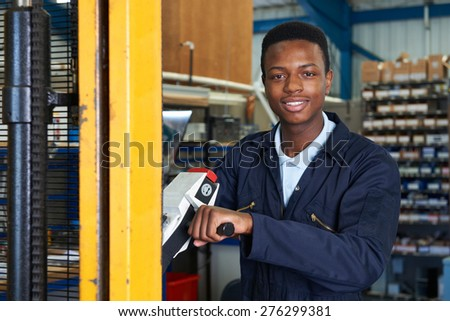 Factory Worker Using Powered Fork Lift To Load Goods - stock photo