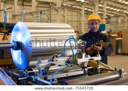 Factory worker using steel coil processing machine - a series of METAL INDUSTRY images. - stock photo