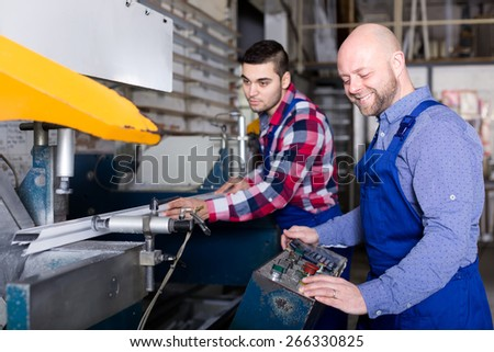 Factory workers cutting aluminum frames on a lathe - stock photo
