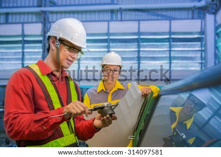 Factory workers discussion inspection report with product and vernier calipers - stock photo