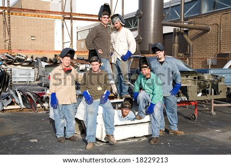 Factory workers surrounded by scrap automobile parts. - stock photo