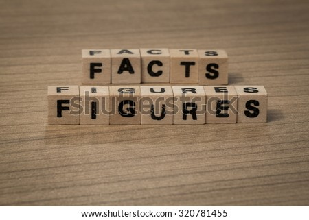 facts and figures written in wooden cubes on a desk