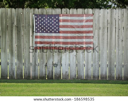 Faded American flag hung on an old wooden fence - stock photo