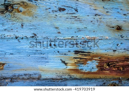 Faded blue paint and rust from nails on wood.