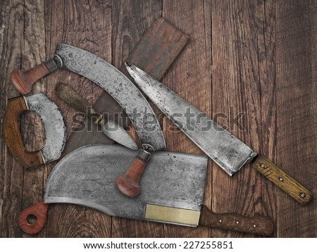 faded colors of a vintage kitchen knives and sharpening tools collage over old wooden table, space for your text - stock photo