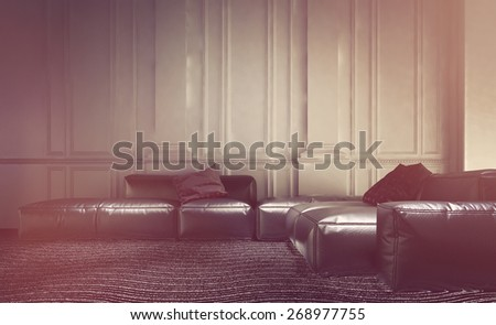 Faded effect living room interior with a comfortable leather modular lounge suite with sofas and settees against a wall with white wood paneling and wainscoting. 3d Rendering.  - stock photo