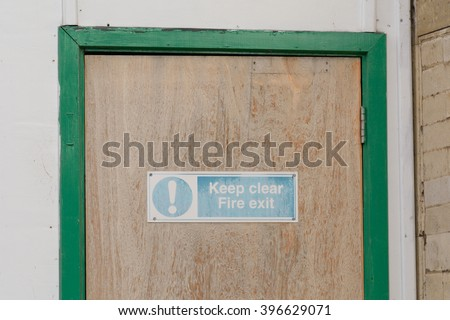 Faded Fire Exit Keep Clear sign on door