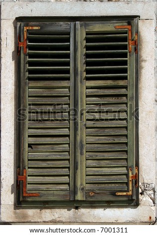 Faded green window blinds with rusty hinges - stock photo