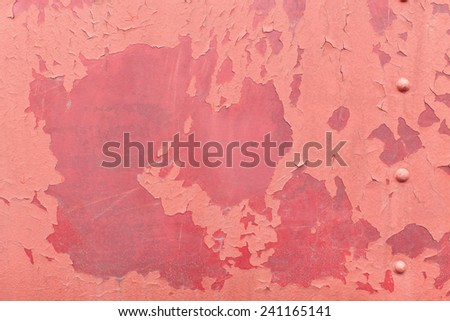 Faded pink paint with red underneath on steel metal with cracks, chips, splits, and paint bubbles with rivet screws. - stock photo