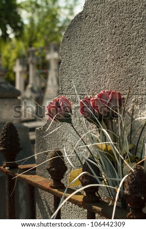 faded plastic flowers and rusty bannister in front of tombstone - stock photo