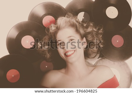 Faded soft retro portrait of a classic pin up girl with curly blond hair lying down on vintage vinyl lp records. Oldies music concept - stock photo