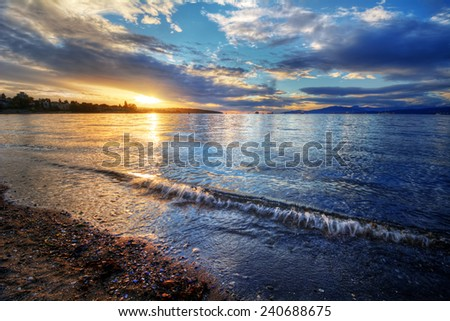 Fading sunlight on the horizon of a sandy riverside shore - stock photo