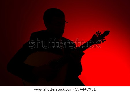 fado musician in silhouette with a portuguese guitar, studio - stock photo