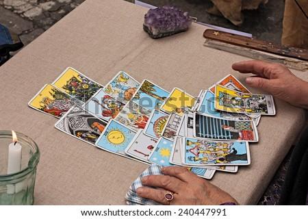 """FAENZA, ITALY - NOVEMBER 4: a woman reading tarots cards at festival """"Fiera di San Rocco"""" on November 4, 2012 in Faenza, RA, Italy.  - stock photo"""
