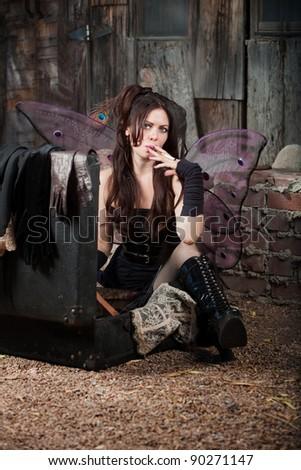 Faery girl sitting on ground smokes cigar - stock photo