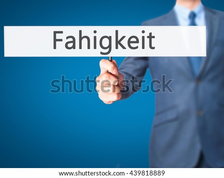 Fahigkeit (Ability in German) - Businessman hand holding sign. Business, technology, internet concept. Stock Photo - stock photo