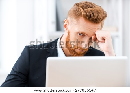 Failed again. Frustrated bearded businessman working on laptop and touching his head while sitting at his working place - stock photo