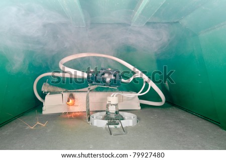 Failure in low voltage transformer installed in a down-light box in the ceiling causing fire - stock photo