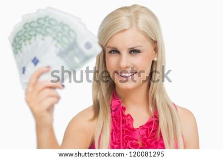 Fair hair woman holding 100 euros banknotes against white background - stock photo