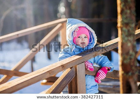 fair-skinned little girl walks in the park in winter in a blue jacket and a pink hat solar frosty weather emotions - stock photo
