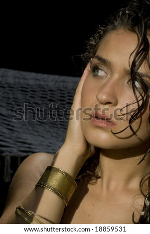 Fair skinned model with wet hair and gold bracelets looking away from the camera? - stock photo