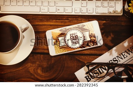 Fair Trade against smartphone on table - stock photo