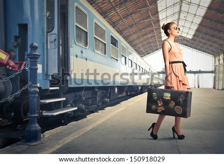 fair traveler with vintage suitcase at the station - stock photo