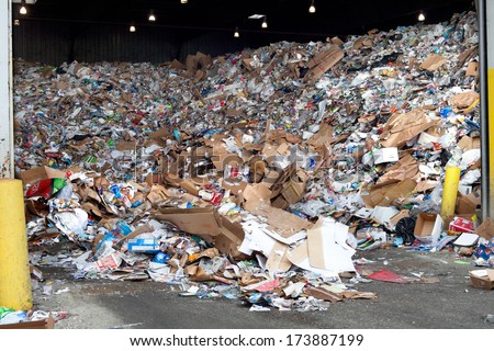 FAIRFAX, VA - DECEMBER 5: A huge load of used paper and plastic lying in a heap in a recycling center on December 5, 2013 in Fairfax, VA. The plastic and paper will be separated on a conveyor belt. - stock photo