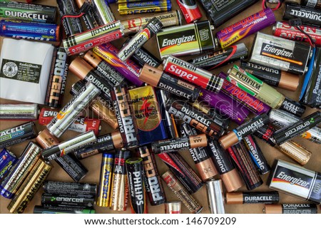 FAIRFAX, VA - JULY 16: Different types of used batteries ready for recycling lying in a heap at a recycling center on July 16, 2013 in Fairfax, VA. Types are AAA, AA, 9-volt and cordless phones. - stock photo