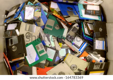 FAIRFAX, VA - NOVEMBER 21: Different types of obsolete floppy disks and diskettes lying in a heap at a recycling facility on November 21, 2013 in Fairfax, VA. Metal and plastic will be separated. - stock photo