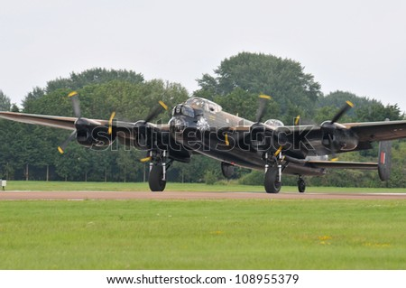 FAIRFORD, UK - JULY 8: Royal Air Force Lancaster aircraft participates in the Royal International Air Tattoo airshow event July 8, 2012 near Cirencester, England. - stock photo
