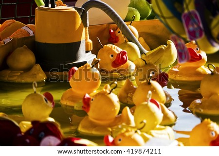 Fairground duck-hook game; close-up of rubber ducks floating in fairground booth; close up; differential focus  - stock photo