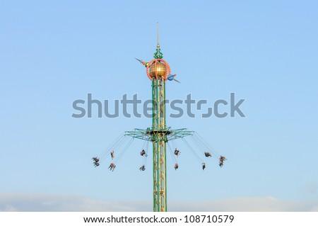 fairground fun fair in tivoli gardens in Copenhagen, Denmark, on a blue summer sky - stock photo