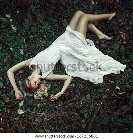 fairitale scene of a woman laying in the forest - stock photo