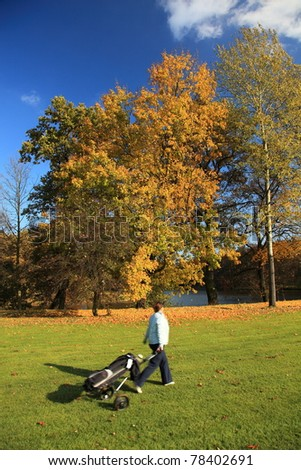 fairway golf course with golfer walking with cart - stock photo
