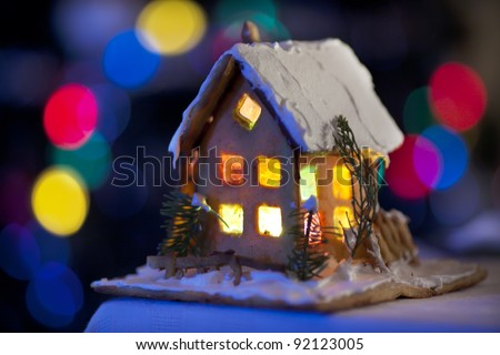 fairy Christmas house cake with candle light inside, narrow depth of field and background lights - stock photo