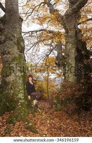 Fairy girl standing in the forest between trees and carpet of red leaves