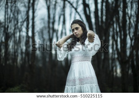 Fairy girl standing on the road in woods. She lightweight white dress