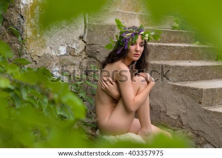 Fairy or nymph woman posing outdoors in green surroundings - stock photo