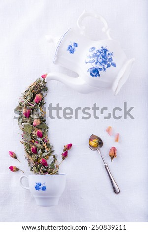 Fairy porcelain white with blue teapot pouring dry herbs and rose tea in the cup, Mad Hatter tea party - stock photo