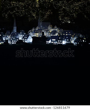 Fairy tale town (village) lit up at night with copy space underneath for your text and message (Christmas, welcome to, etc) - stock photo