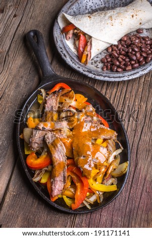 Fajitas, a sizzling plate full of grilled steak, peppers and onions. - stock photo