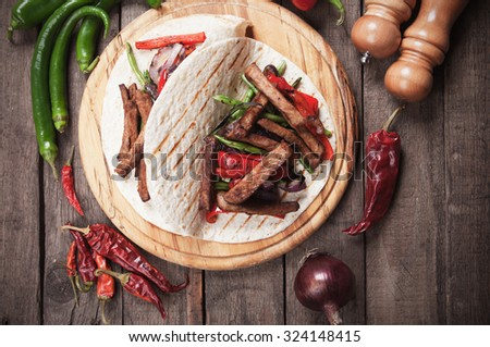 Fajitas, mexican beef stripes with vegetables in tortilla wrap - stock photo