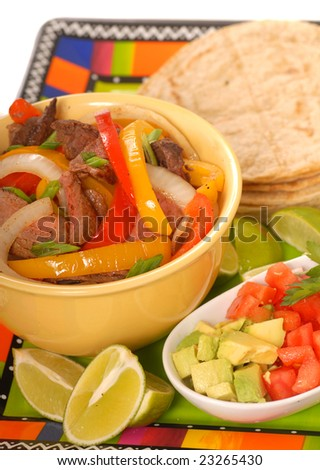 Fajitas platter containing beef, peppers, onions and condiments
