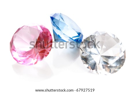 Fake colored gems in the shape of large diamonds are isolated on a white background with reflections. - stock photo