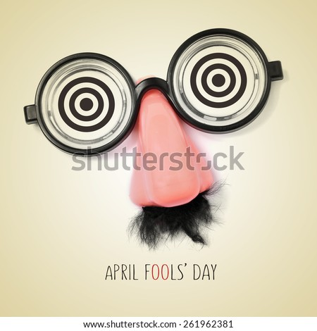 fake eyeglasses, nose and mustache and the sentence april fools day written in a beige background, with a retro effect - stock photo