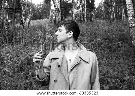 Fake farmer smells flower on meadow retro photo